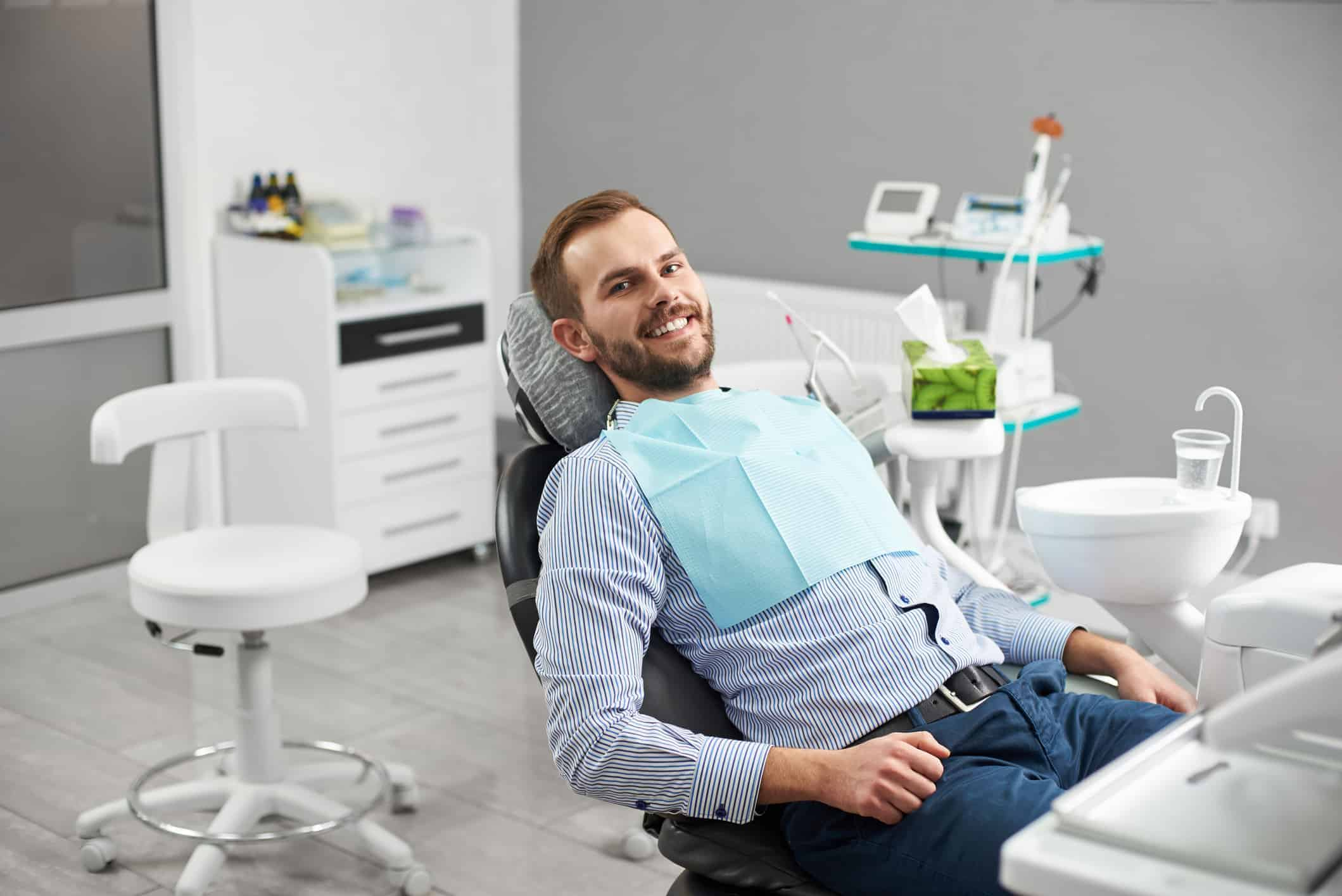 Portrait of happy patient in dental chair. Modern dentistry with the use of new technologies